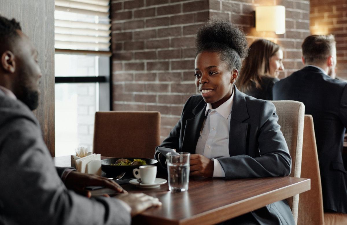 Two People Demonstrating Good Coffee Meeting Etiquette In Coffee Shop